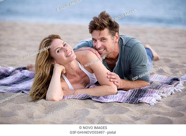 Smiling Mid-Adult Couple Laying on Blanket at Beach
