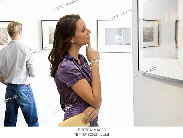 Woman looking at picture in art gallery