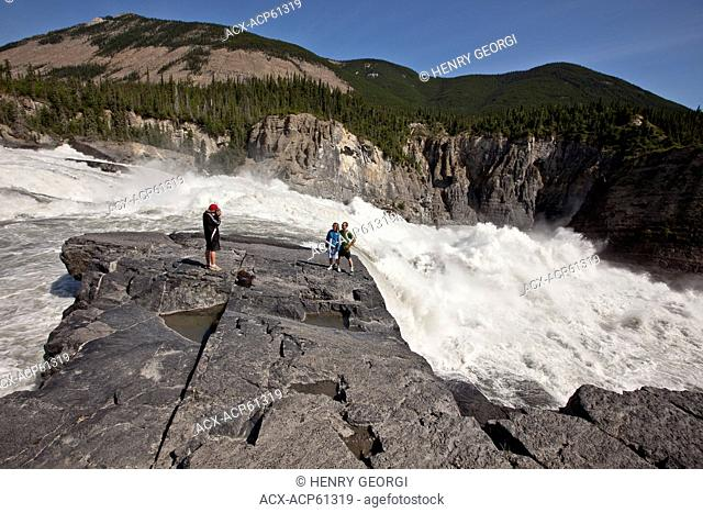 Family enjoy view at Sluicebox son photographing parents, Virginia Falls, Nahanni National Park Preserve, NWT, Canada