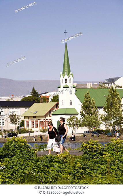 Two women walking by Tjornin lake, Frikirkjan church in the background  Reykjavik Iceland