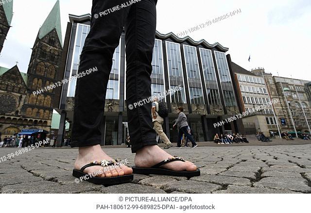 ILLUSTRATION - 12 June 2018, Germany, Bremen: A woman wearing flip-flops standing at the Marktplatz outside the Bremen Buergerschaft legislative assembly