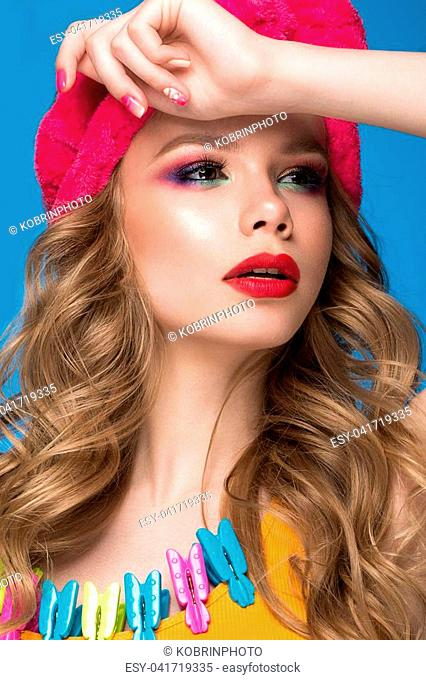 Bright cheerful girl in a home hat, colorful make-up, curls and pink manicure. Beauty face. Photo taken in the studio