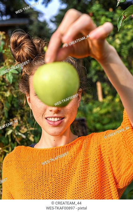 Young woman hiding behind green apple