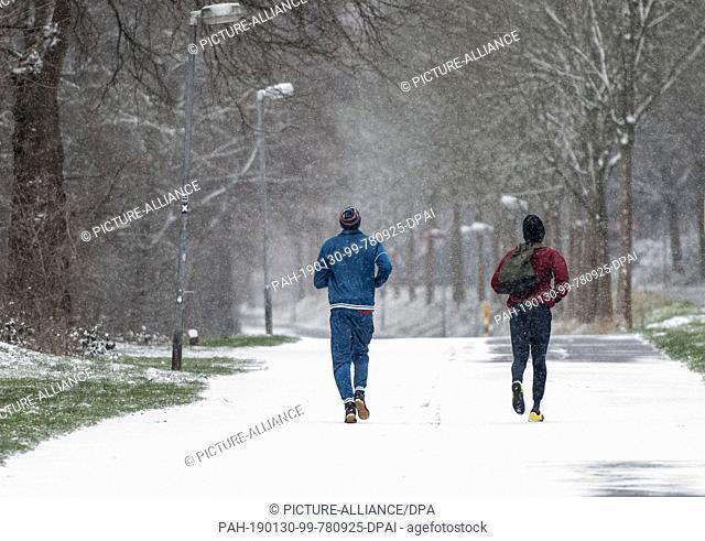 30 January 2019, North Rhine-Westphalia, Herdecke: Two joggers on their way along the Ruhr in light snowfall Photo: Bernd Thissen/dpa