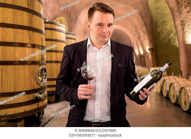 Winemaker or sommelier inspecting quality of red wine, standing near bottles racks in winery vault