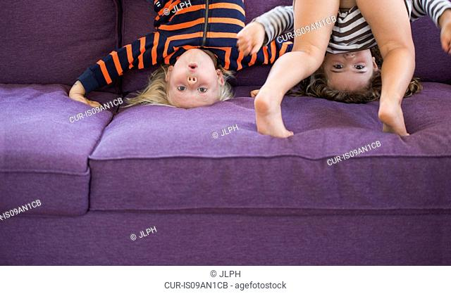Portrait of young boy and girl doing headstand on sofa