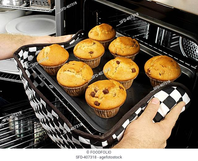 Man taking muffins out of the oven