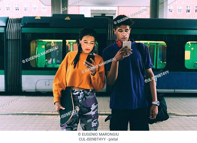 Brother and sister texting at tram stop, Milan, Italy