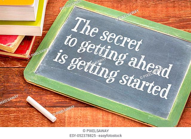 The secret to getting ahead is getting started - white chalk text on a slate blackboard with a stack of books against rustic wooden table