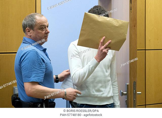 Defendent Sanel M. (R) enters a secured area of the court room at the regional court in Darmstadt, Germany, 24 April 2015