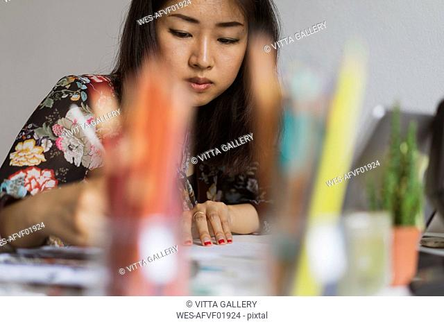 Illustrator drawing at work desk in an atelier