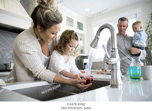 Mother helping daughter wash berries in kitchen sink