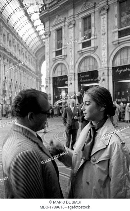 inside the Galleria Vittorio Emanuele II the Italian director Antonio Pietrangeli, who holds a cigarette in his hands, talk with the french actress Jacqueline...