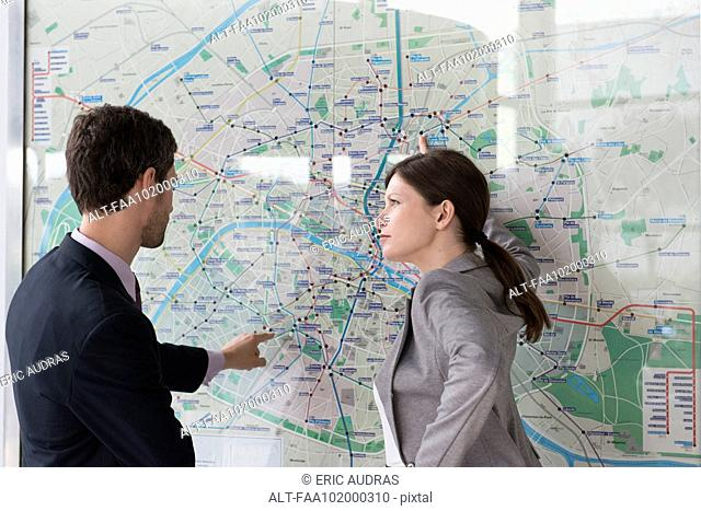 Man and woman planning route on Paris metro