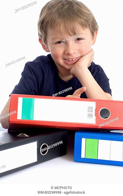 little boy leaning on a stack of files with a smile