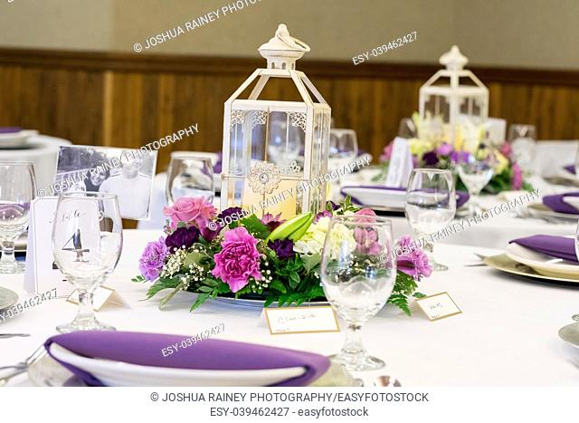 Wedding reception centerpieces of candle lanterns on tables decorated with flowers from a local florist