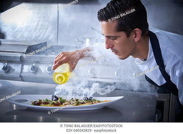 Chef preparing octopus recipe in kitchen with smoke and oil