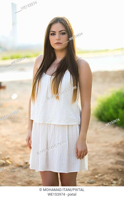 Beautiful young woman with long dark hair wearing a dress standing outdoors staring