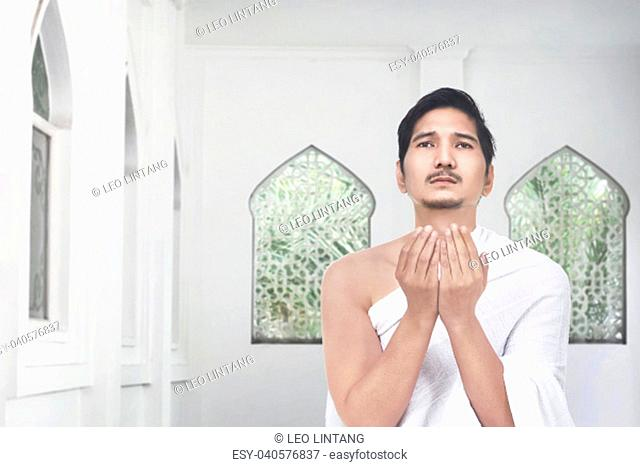 Handsome asian pilgrim praying to god in the mosque