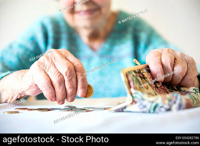 Detailed closeup photo of elderly 96 years old womans hands counting remaining coins from pension in her wallet after paying bills