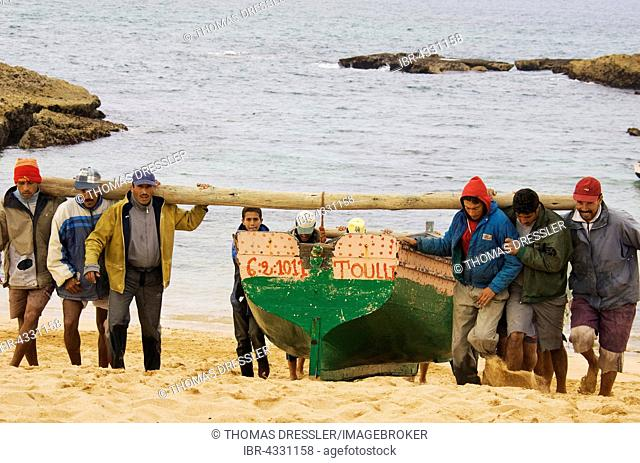 Fishermen carrying fishing boats up onto the sandy beach of Oualidia, a seaside town and fishing port at the Atlantic Ocean south of El Jadida, Morocco