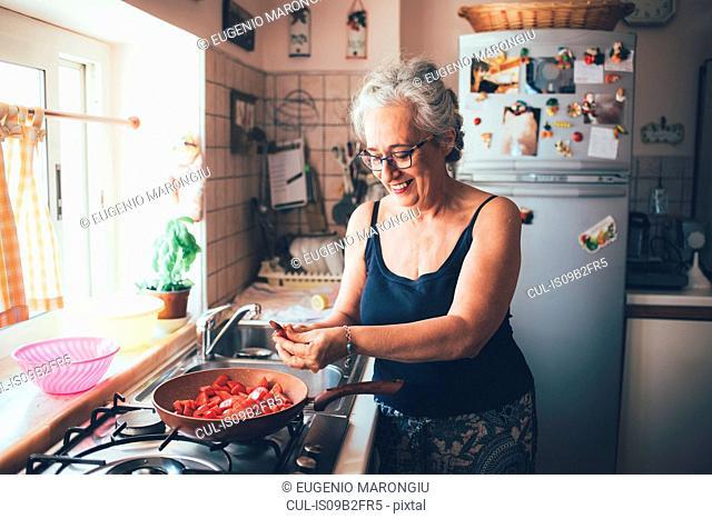 Woman chopping tomatoes into saucepan smiling