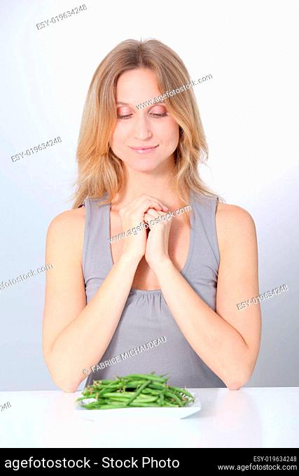 Unhappy woman in front of green beans