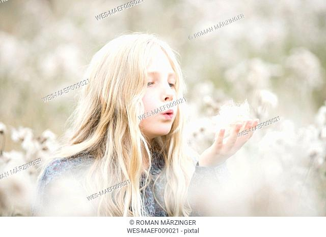 Portrait of girl standing in a field blowing seeds out off her hand