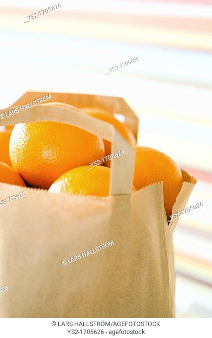 Brown paper bag full of oranges