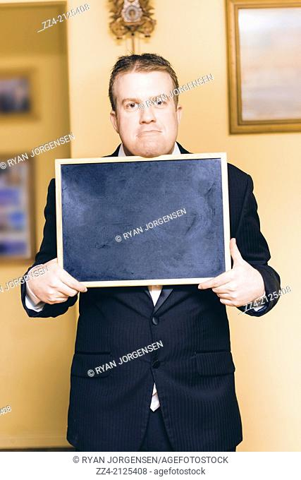 Funny groom holding an empty copy space black board with sad expression on wedding day. Cold feet