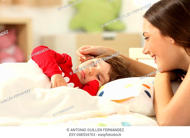 Affectionate mother looking at her toddler girl sleeping in a bed in her room at home