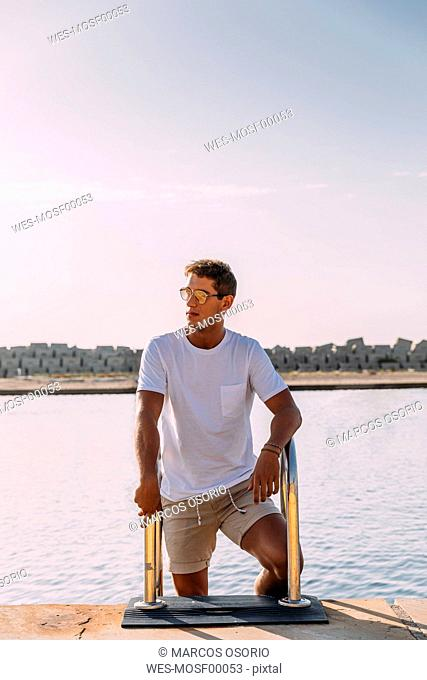 Young man on a pier at swimming area