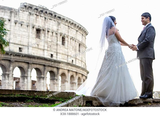 Newlyweds in front of the roman Colosseum in Rome Italy