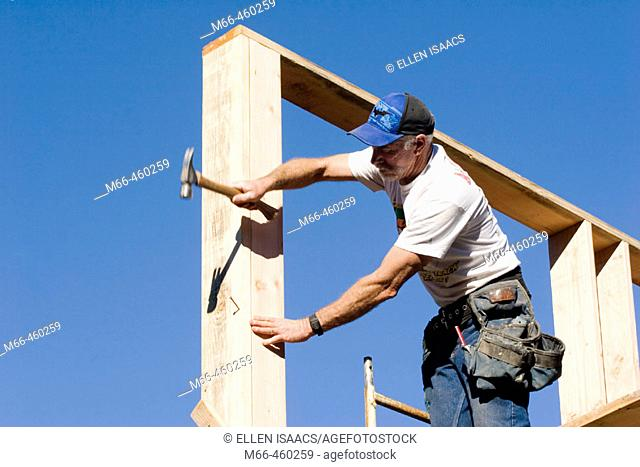 Carpenter reaching to hammer a nail into the corner stud of a two-story room while standing on scaffolding