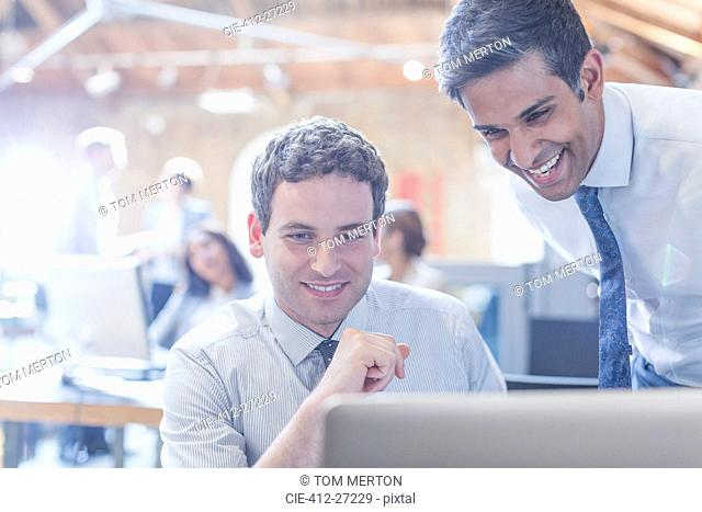 Businessmen working at laptop in office
