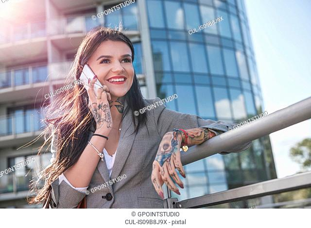 Businesswoman outdoors, using smartphone, smiling, tattoos on hands