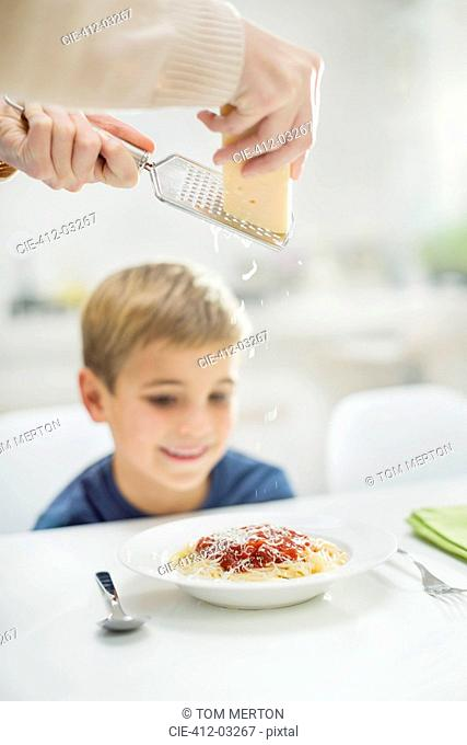 Mother grating cheese over son's spaghetti