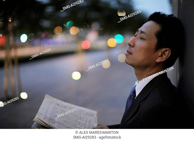 Mature man leaning against a wall with eyes closed in the evening