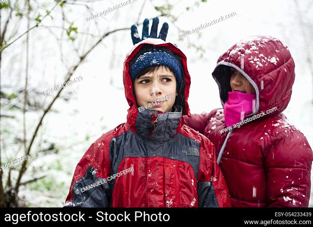 Children in the forest while snowing