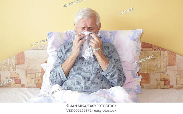 Sick senior man coughing and blowing nose in bed