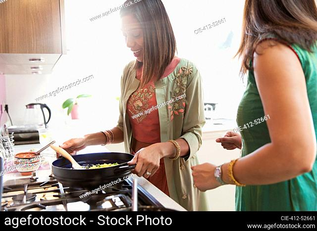 Indian woman in sari cooking food at stove in kitchen