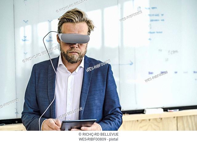 Businessman standing in office, using VR glasses and digital tablet