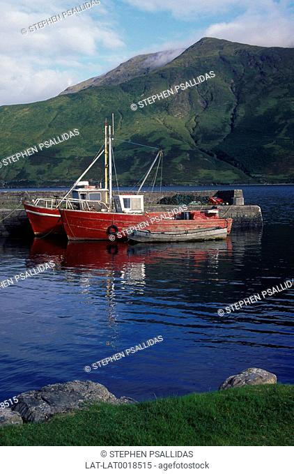 Two red fishing boats moored at head of Killary Harbour. An inlet like a fjord. Green hills. Landscape