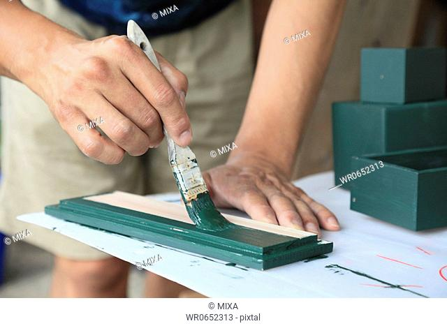 Cabinet Maker Putting Paint on Wood