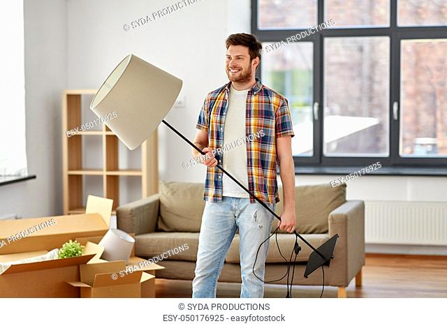 happy man with floor lamp moving to new home