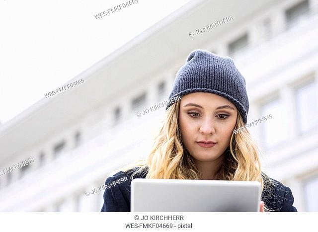 Portrait of young woman using tablet outdoors