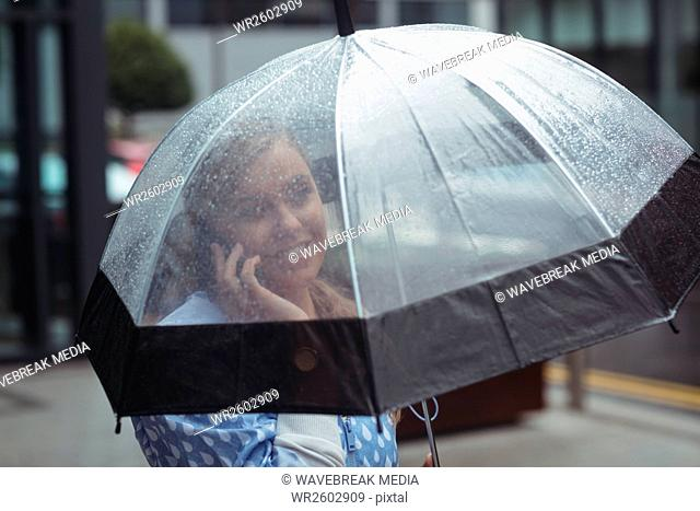Woman holding umbrella while talking on mobile phone