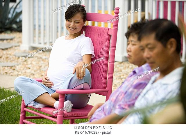 Pregnant woman sitting on rocking chair with her parents in foreground