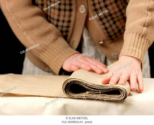 Cropped close up of young female designer's hands folding burlap fabric