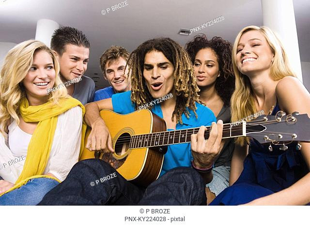Man sitting with his friends and playing a guitar